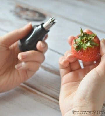left hand holding strawberry huller right hand holding strawberry