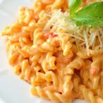 roasted red pepper macaroni and cheese on a white place with shredded parmesan and parsley garnish