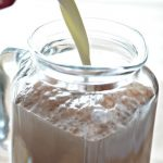 milk pouring into homemade chocolate milk in glass pitcher