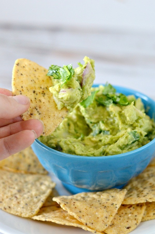 the best guacamole in a blue porcelain bowl with tortilla chips