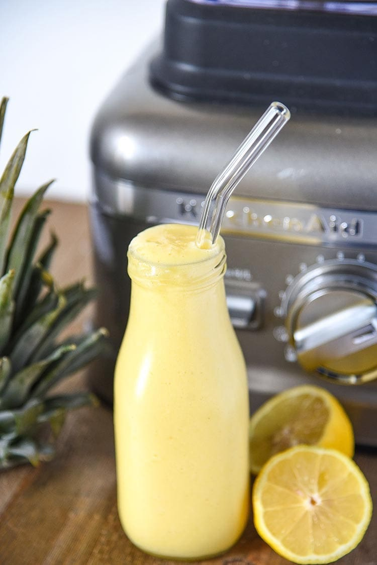 pineapple lemonade in a glass jar with glass straw in front of a kitchenaid blender with lemons on the right and pineapple top on the left
