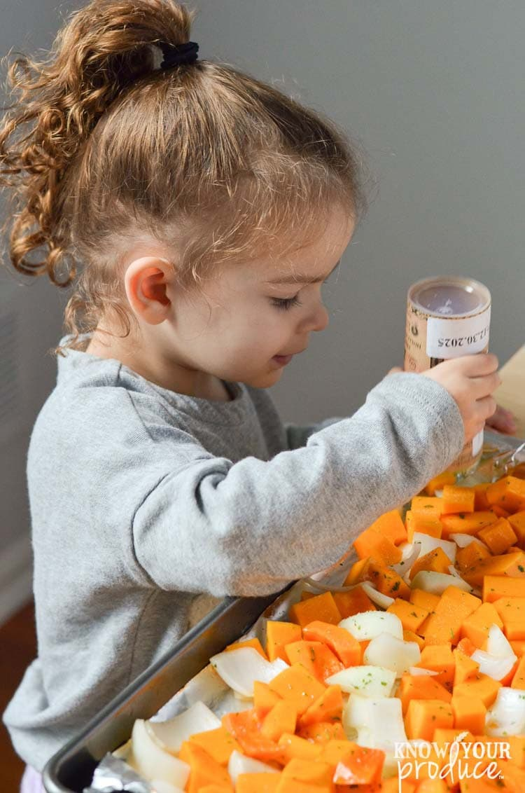 little girl shaking salt onto chopped butternut squash and onions on a sheet pan