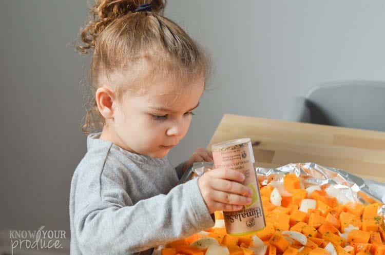 little girl seasoning chopped butternut squash and onions on a sheet pan