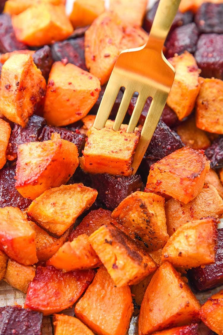 roasted beets and sweet potatoes on a sheet pan with a fork