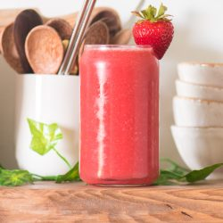 strawberry watermelon juice in a glass cup with stacked bowls to the back right and a cup with wooden spoons and reusable straws to the left and greenery around