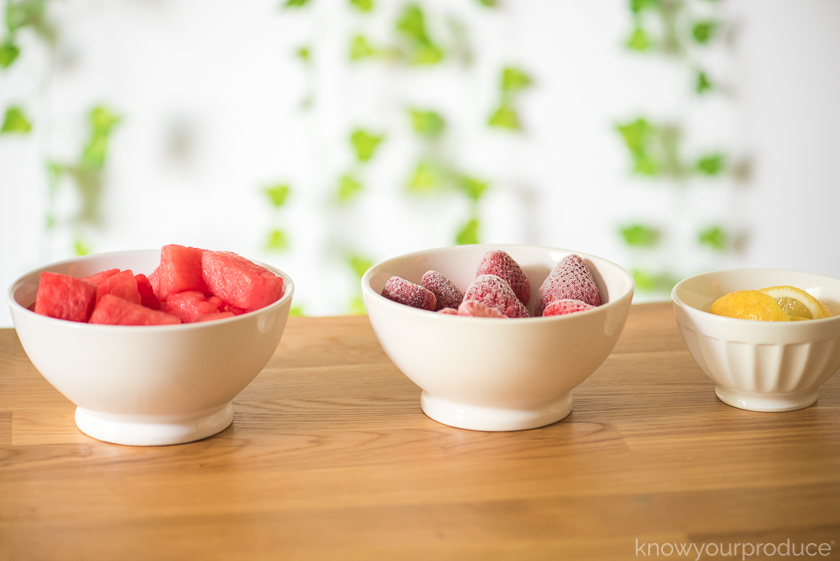 3 bowls on a table one with watermelon one with frozen strawberries and one with cut lemon wedges with greenery in the background