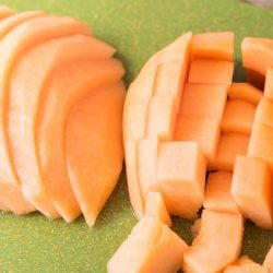 how to cut a cantaloupe cubes and wedges on a green cutting board