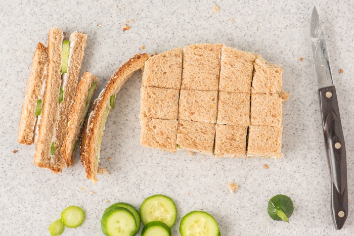 removing crusts from cucumber sandwich