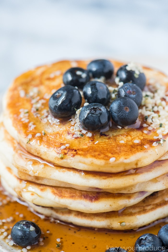 fresh blueberry pancakes with fresh blueberries covered in maple syrup on a plate
