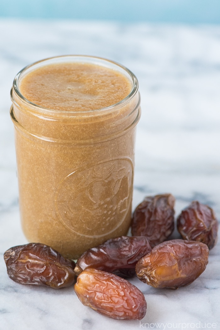 date syrup in a mason jar with fresh dates on a marble board