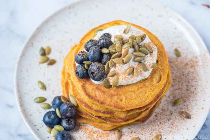 pumpkin pancakes on a plate with blueberries sunflower seeds and greek yogurt