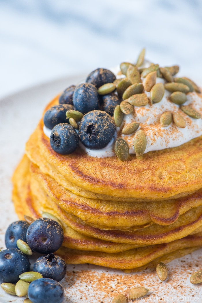 stacked pumpkin pancakes on a plate with blueberries sunflower seeds and greek yogurt
