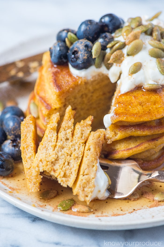 pumpkin pancakes cut on a fork on a plate with blueberries sunflower seeds and greek yogurt