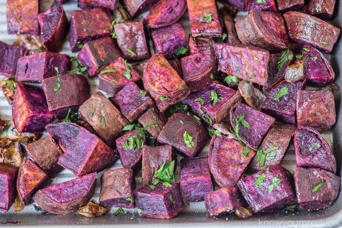 roasted purple sweet potatoes on a sheet pan with parsley