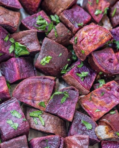 roasted purple sweet potatoes with parsley on a sheet pan