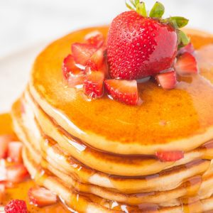 strawberry pancakes covered in maple syrup on a plate