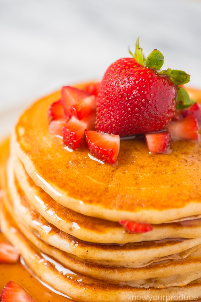 strawberry pancakes stacked on a plate with maple syrup