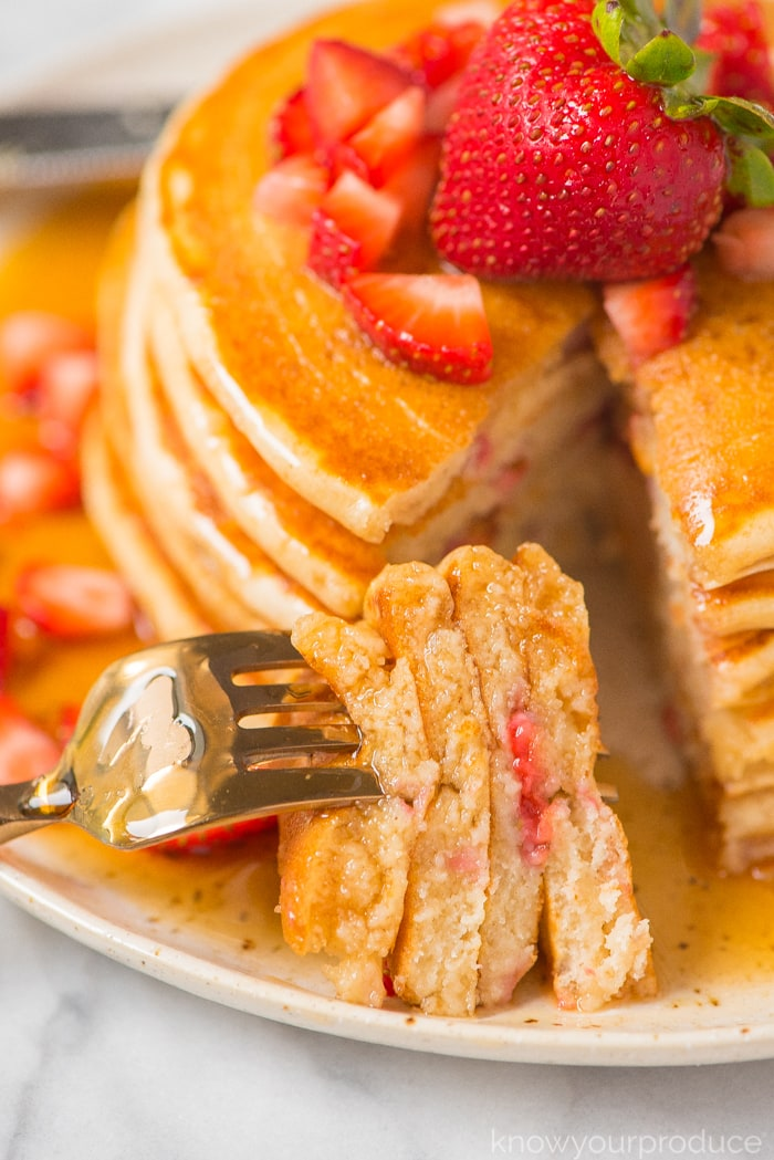 strawberry pancakes cut with a fork