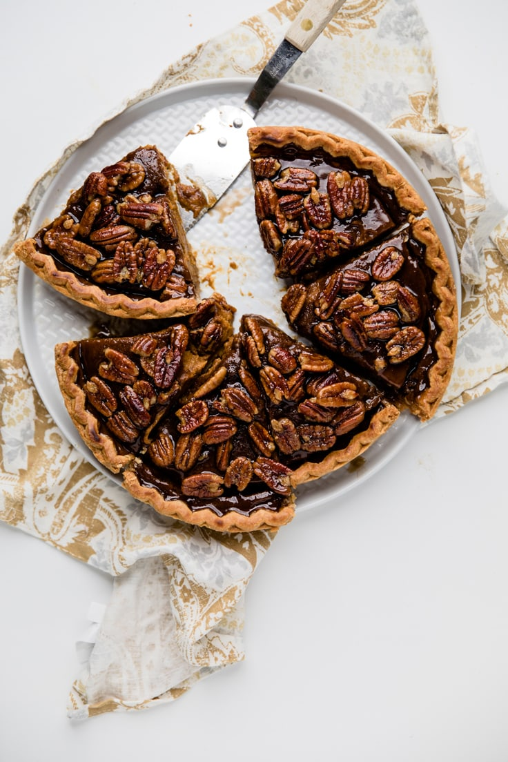 cut pecan pie on a pie plate with serving knife on white and gold napkin