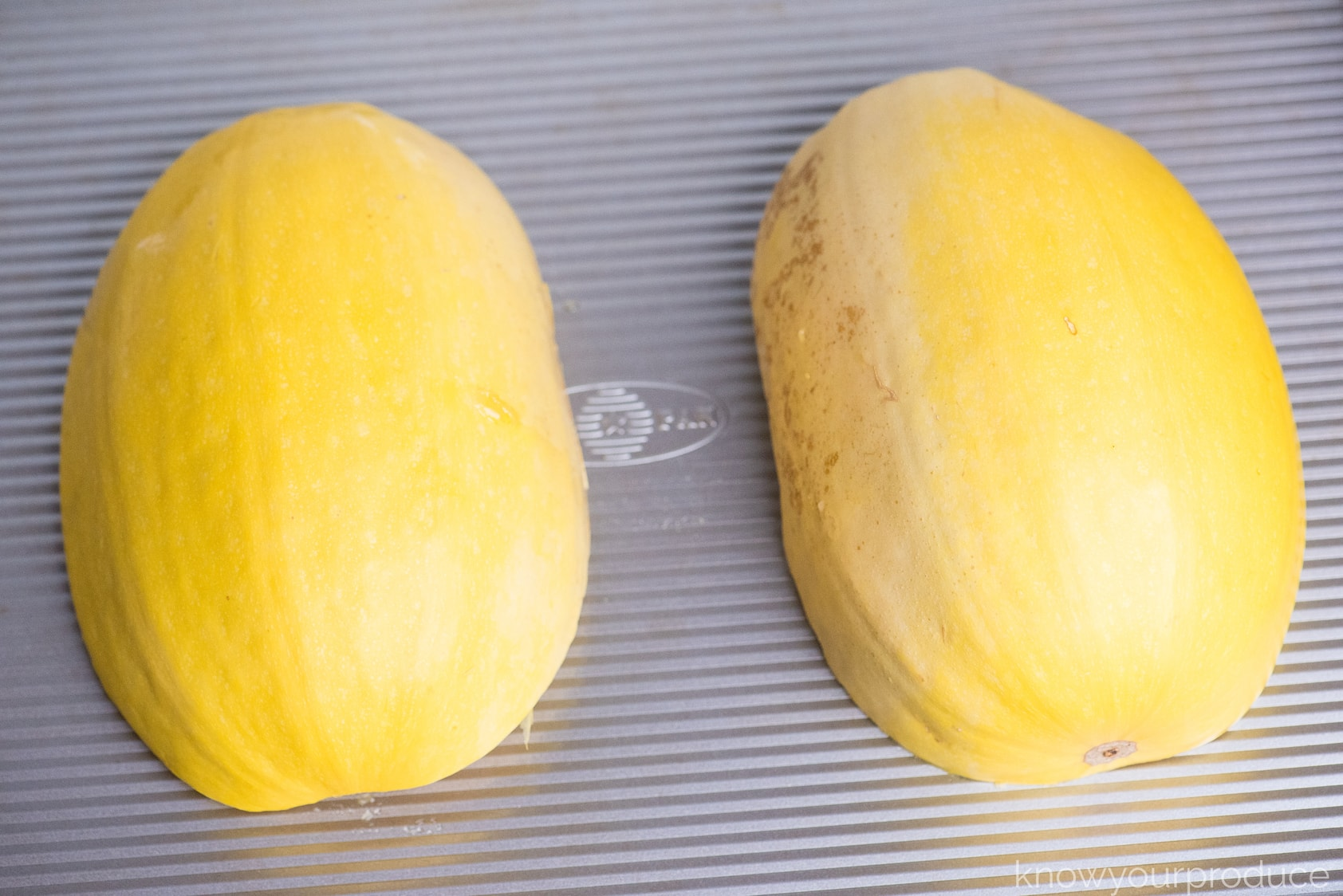 two spaghetti squash halves cut and placed face down on a baking sheet