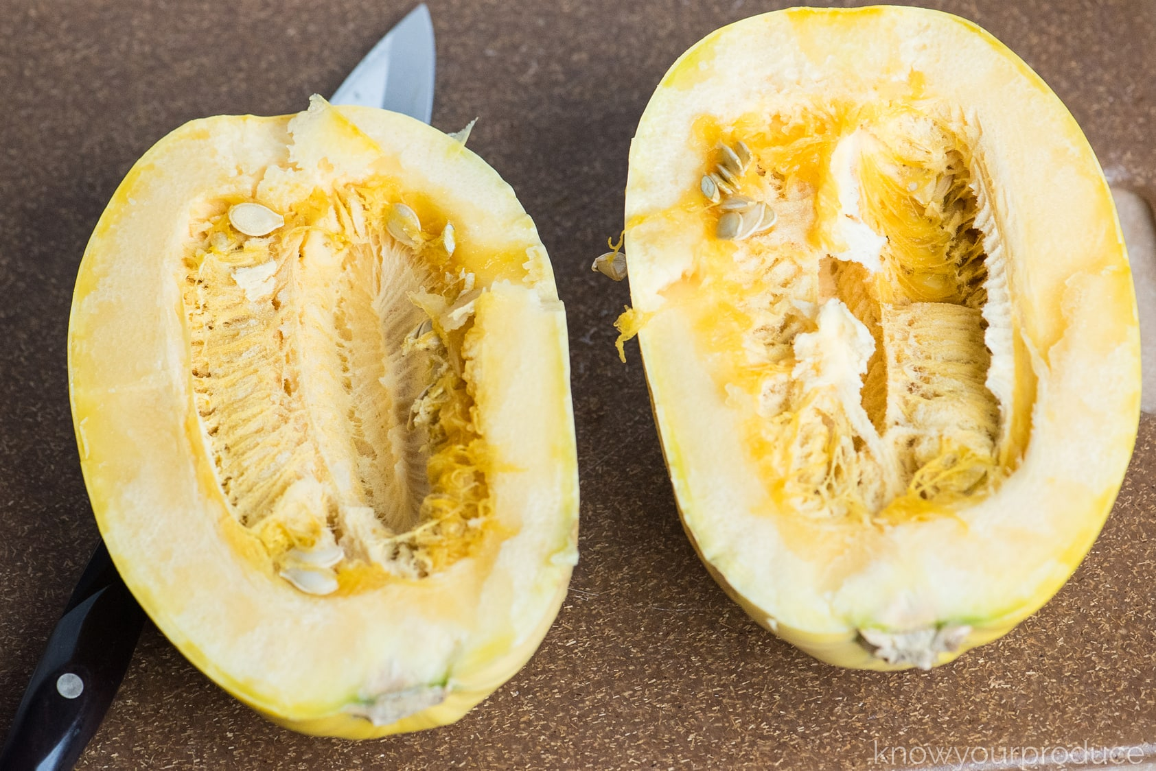 spaghetti squash cut in half on cutting board with seeds in