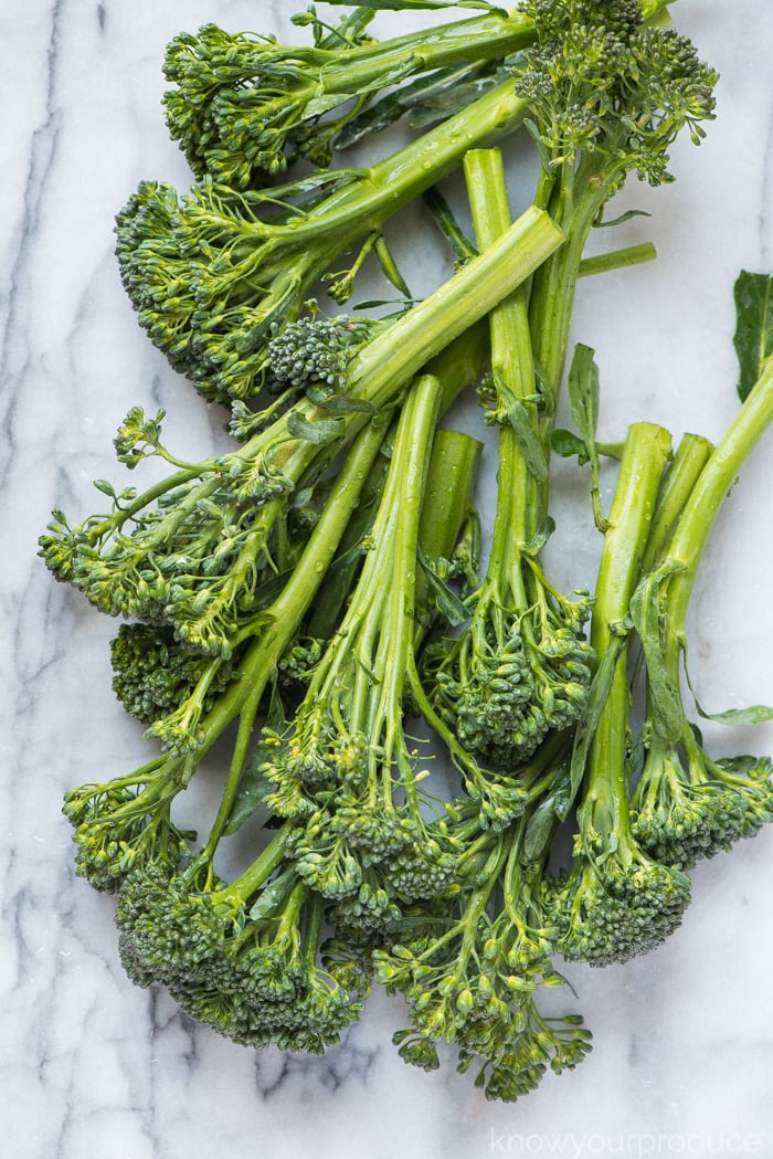 fresh broccolini on a marble pastry board