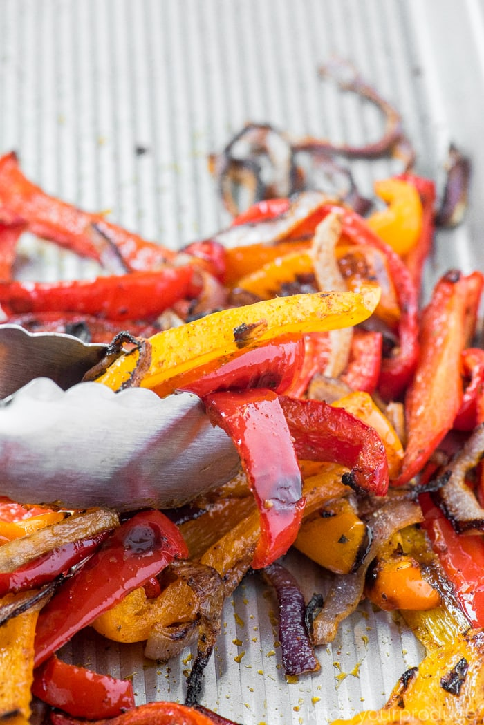 roasted peppers and onions with tongs on a sheet pan