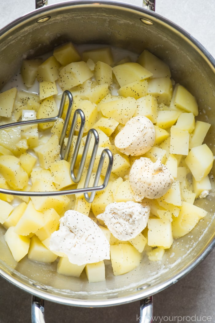 potato masher mashing potatoes in a pot with vegan milk, vegan butter, and vegan cream cheese