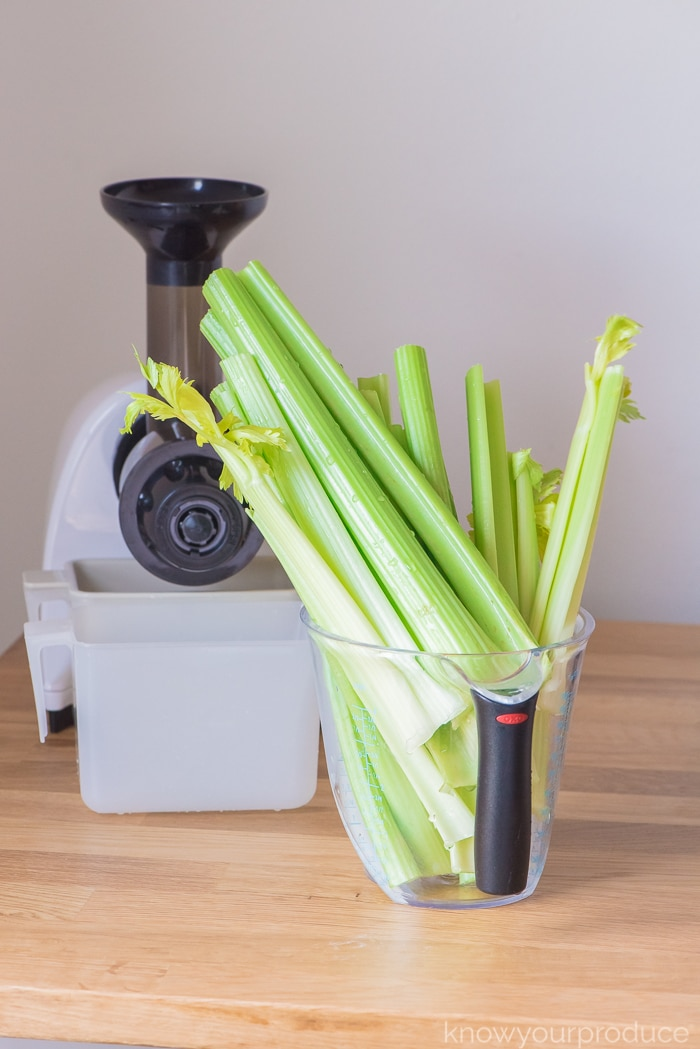 washed celery for celery juice recipe in a large measuring cup with juice in the background