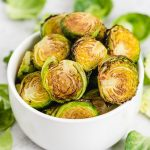 balsamic roasted brussels sprouts in a bowl with brussels sprout leaves scattered