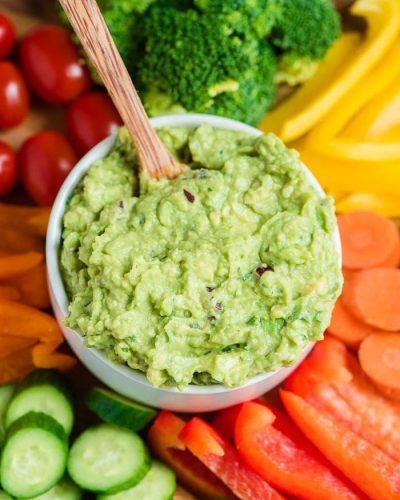 guacamole in a bowl with wooden spoon in middle of vegetable platter