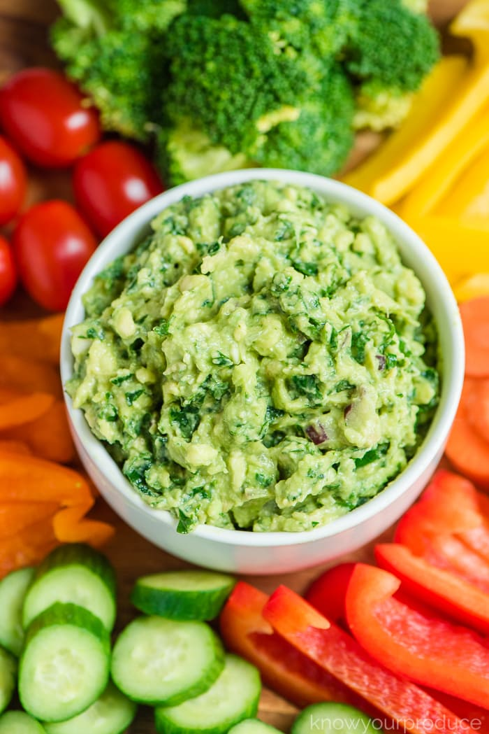 kale guacamole in white bowl with veggie platter