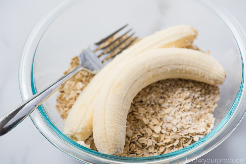 bananas and oatmeal in a glass bowl with fork