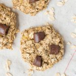 banana oatmeal cookies with scattered rolled oats on a cloth napkin