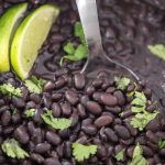instant pot black beans with stainless steel spoon inside and garnished with lime and cilantro