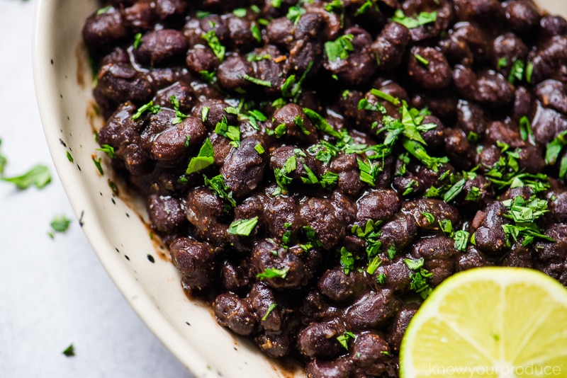 mexican black beans garnished with cilantro and lime in a bowl