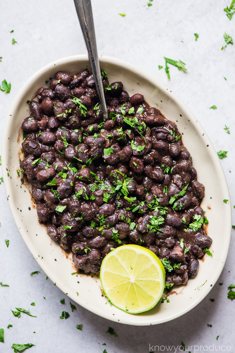 mexican black beans with spoon and half lime in a bowl