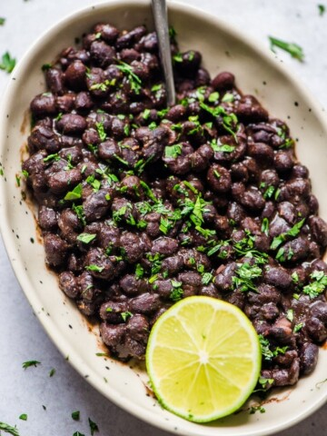 mexican black beans in bowl with spoon, lime wedge, and cilantro garnish