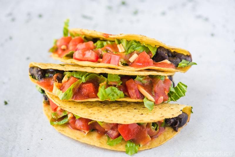 siete grain free taco shells stuffed with black beans lettuce pico de gallo and vegan cheddar cheese