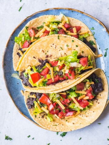 vegan tacos with black beans, lettuce, vegan cheese shreds, and fresh pico de gallo on a blue plate