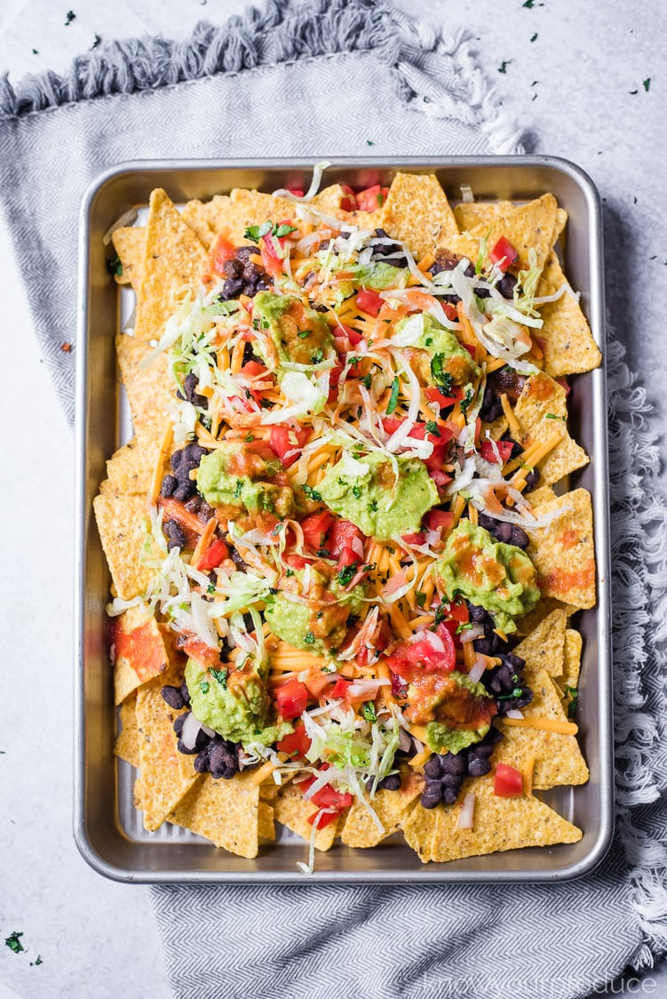 vegan nachos on a baking sheet on a gray napkin