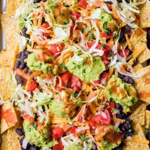 vegan nachos with black beans on a baking sheet