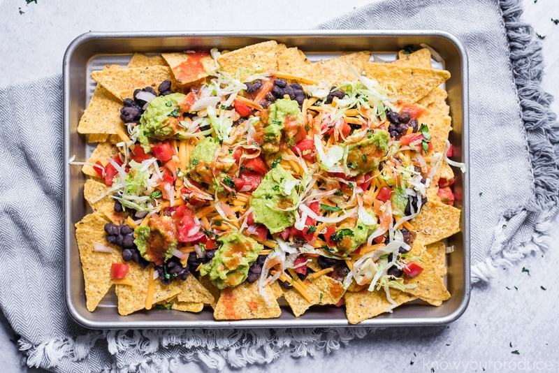 nachos on a baking sheet over a gray napkin