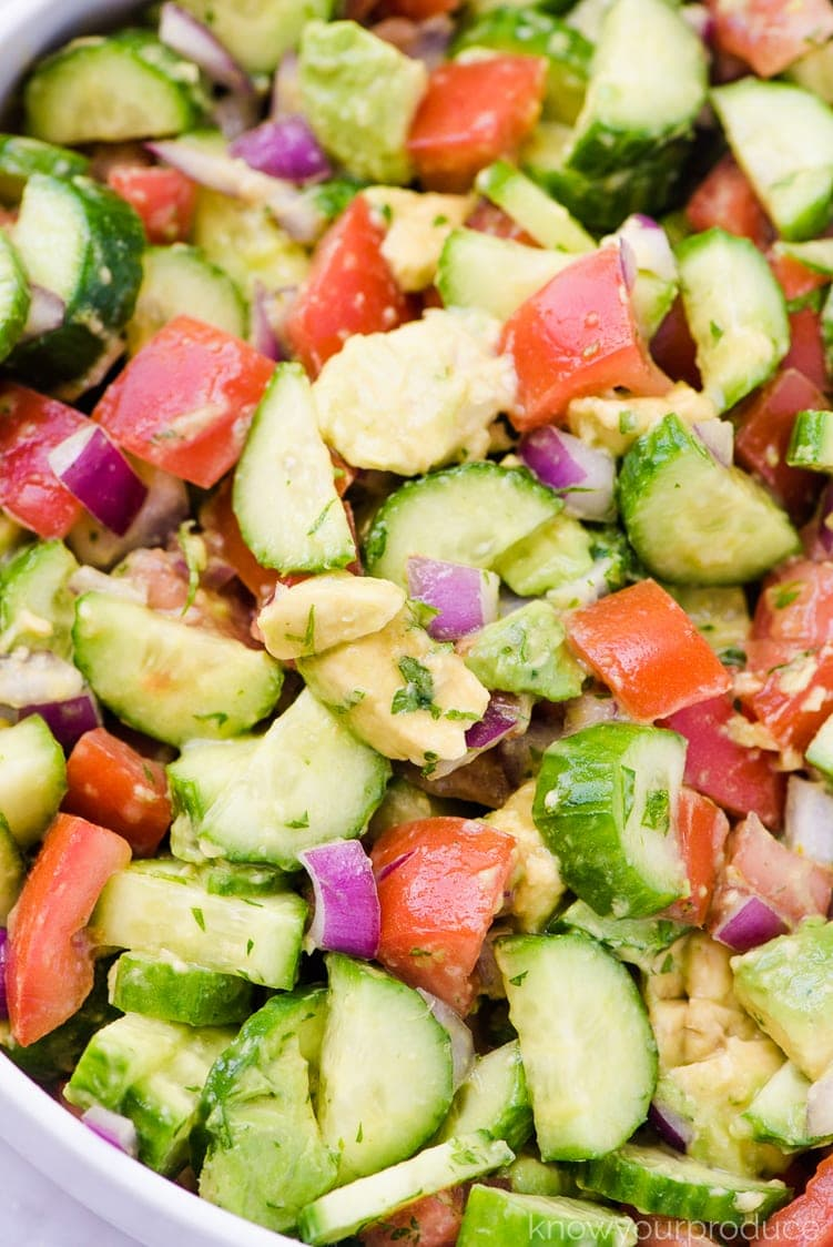 sliced cucumbers chopped tomatoes and avocados in a bowl