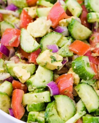 chopped cucumber tomato salad with avocado in a bowl