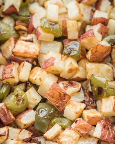 roasted potatoes peppers and onions on a sheet pan