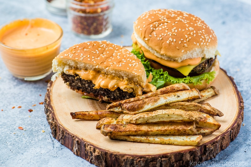 veggie burgers on a wooden board with fries