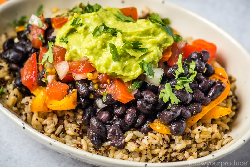 loaded vegan burrito bowl with quinoa brown rice black beans peppers and onions and guacamole