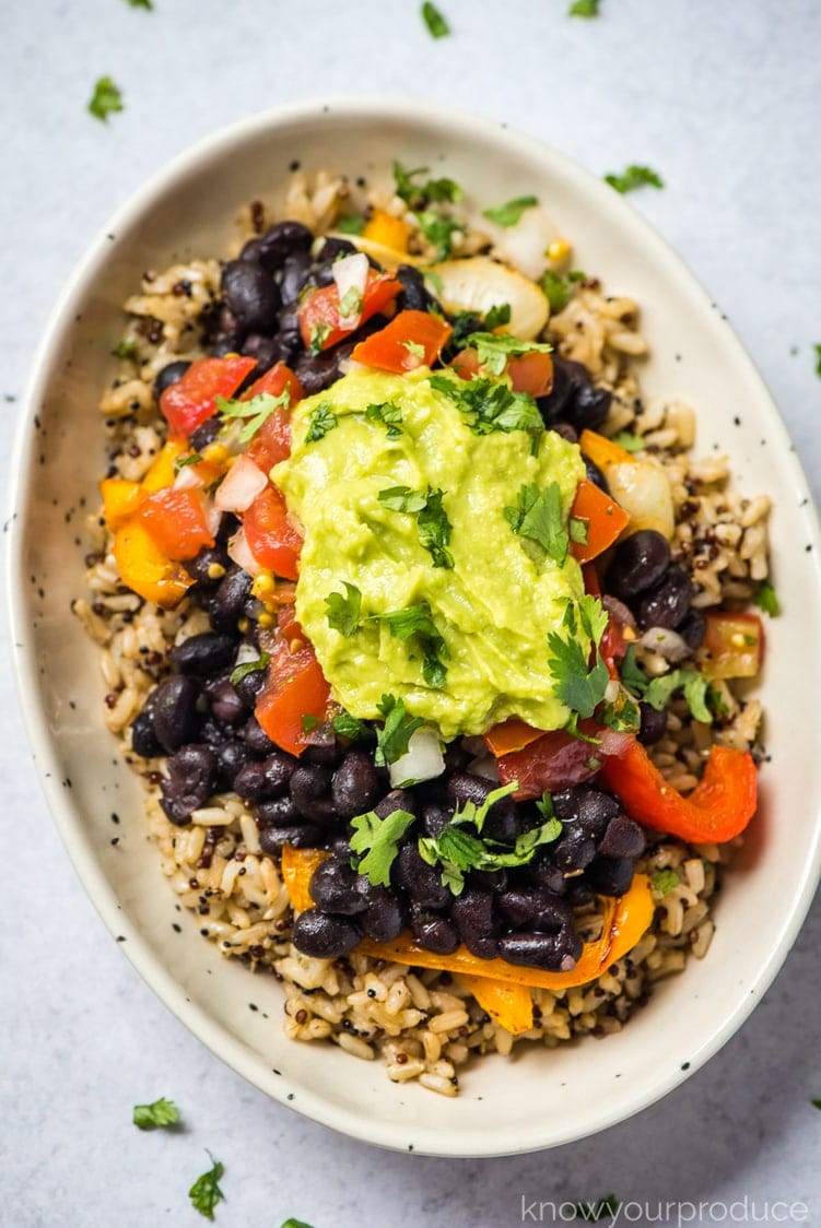 vegan burrito bowl with quinoa brown rice topped with guacamole