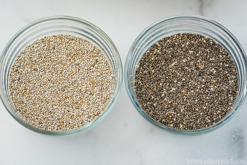 white chia seeds in a glass bowl to the left and black chia seeds in a glass bowl to the right
